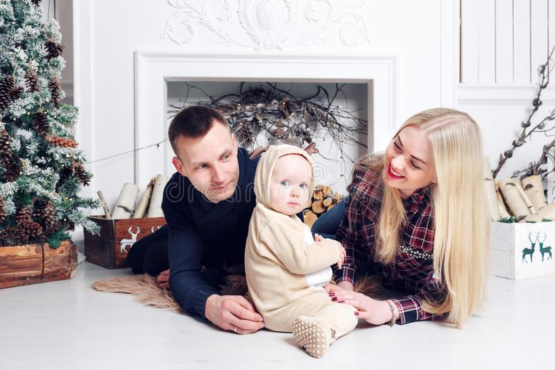Happy family at Christmas. The parents and the baby lying on the floor and smiling. stock images