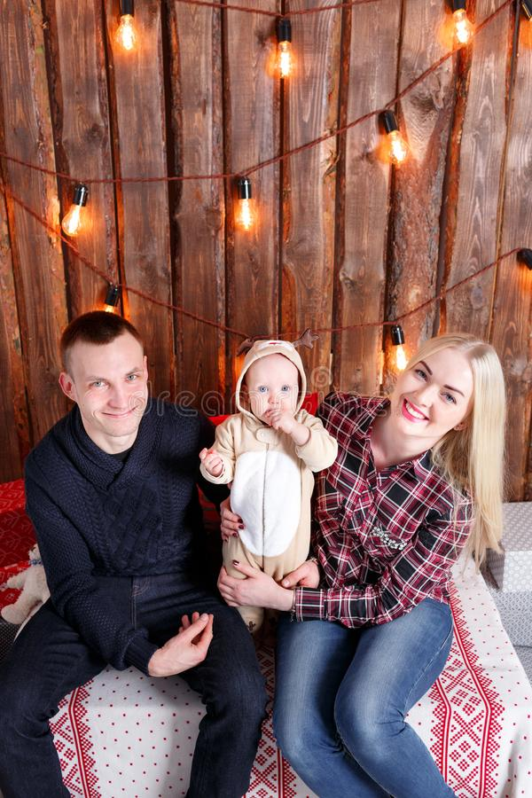 Happy family at Christmas. The parents and the baby sitting. Wall of wooden planks and garland stock images