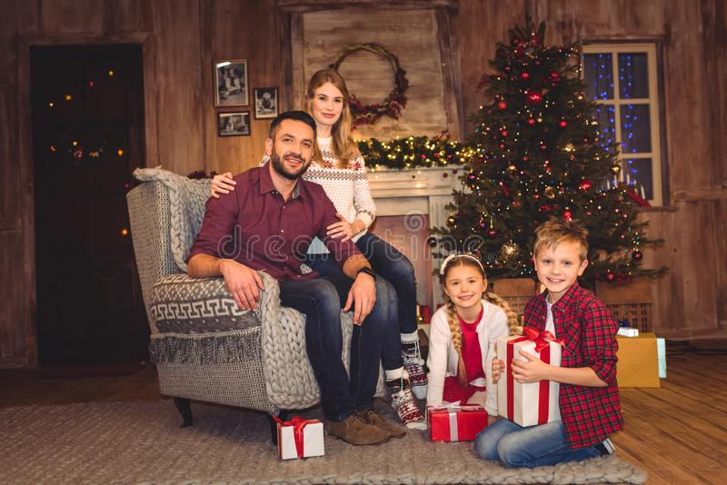 Happy family sitting with christmas presents and looking. At camera stock images