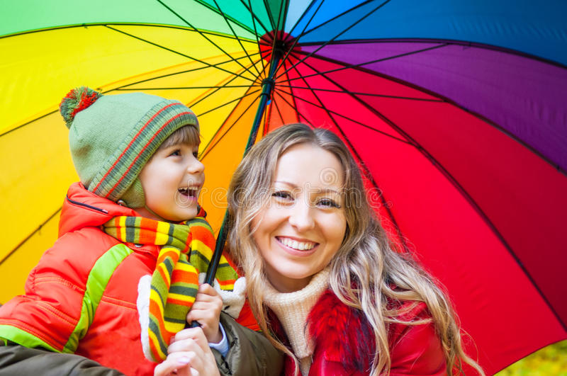 Happy family with colorful umbrella in autumn park stock photography