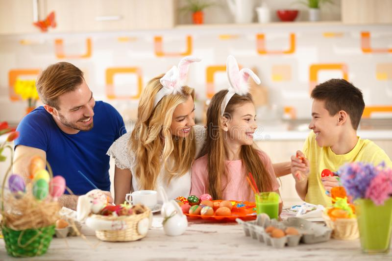 Happy family coloring eggs for Easter royalty free stock photography
