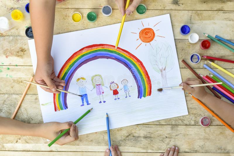 Happy family concept. Co-creation. Children hands draw on a sheet of paper: father, mother, boy and girl hold hands against stock photos