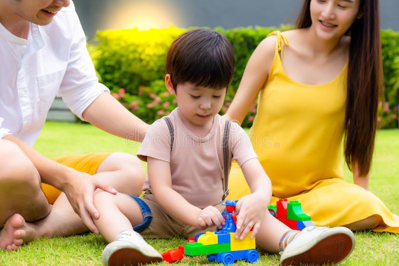 Happy family concept. Cute little boy or son playing toy, dad and mother cheering their son with smiley faces. Dad, mom and son royalty free stock image