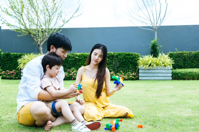 Happy family concept. Dad and mom teaching, playing toy with son together at garden around house with smiley faces. Cute boy is. First child of family and he stock image