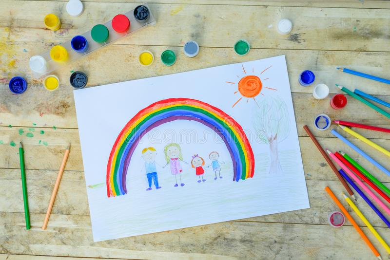 Happy family concept. Drawing on wooden table: father, mother, boy and girl hold hands against background of rainbow and sunny sky royalty free stock photography