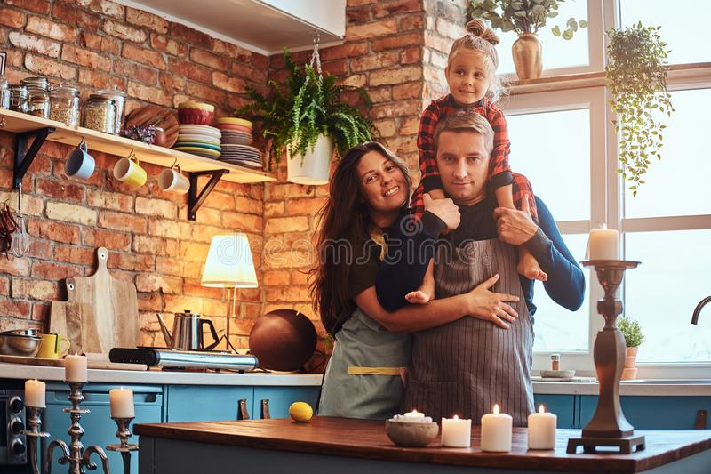 Mom dad and little daughter together in loft style kitchen at morning. royalty free stock image