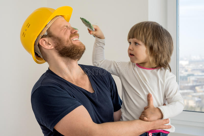 Happy family, construction worker in helmet and small child. With paint brush royalty free stock photography