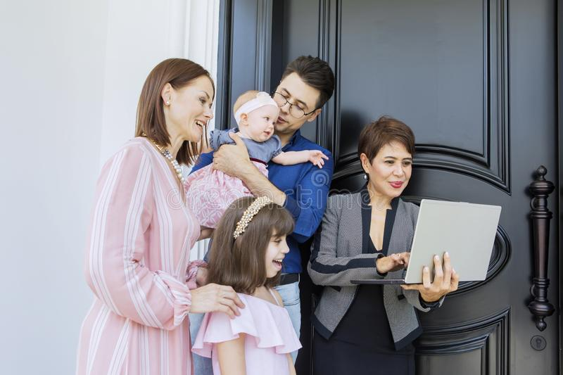 Happy family consulting with their real estate agent. While standing together near a door stock images