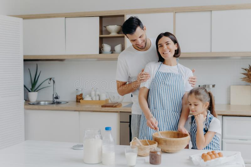 Happy family cook together at kitchen. Father, mother and dauther busy preparing delicious meal at home. Husband embraces wife who royalty free stock image