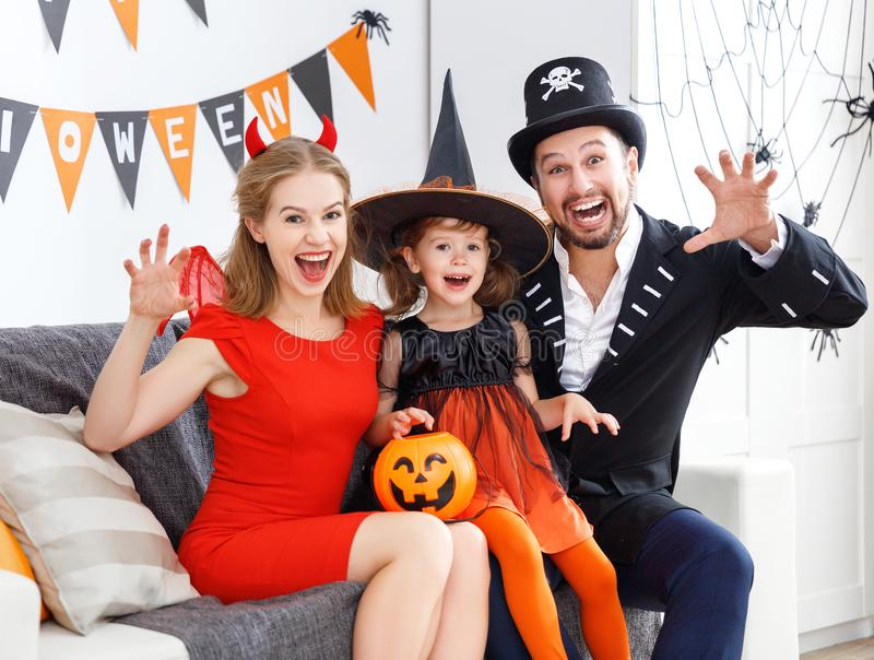 Happy family in costumes getting ready for halloween at home. A happy family in costumes getting ready for halloween at home royalty free stock photography