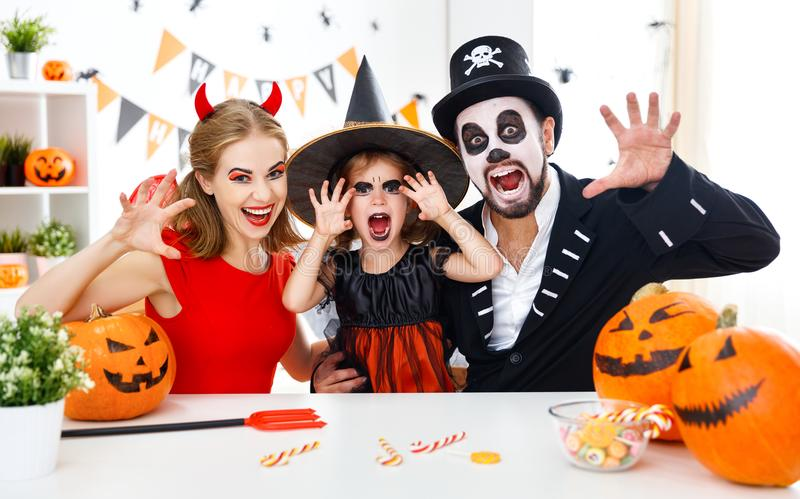 Happy family in costumes getting ready for halloween at home. A happy family in costumes getting ready for halloween at home stock images