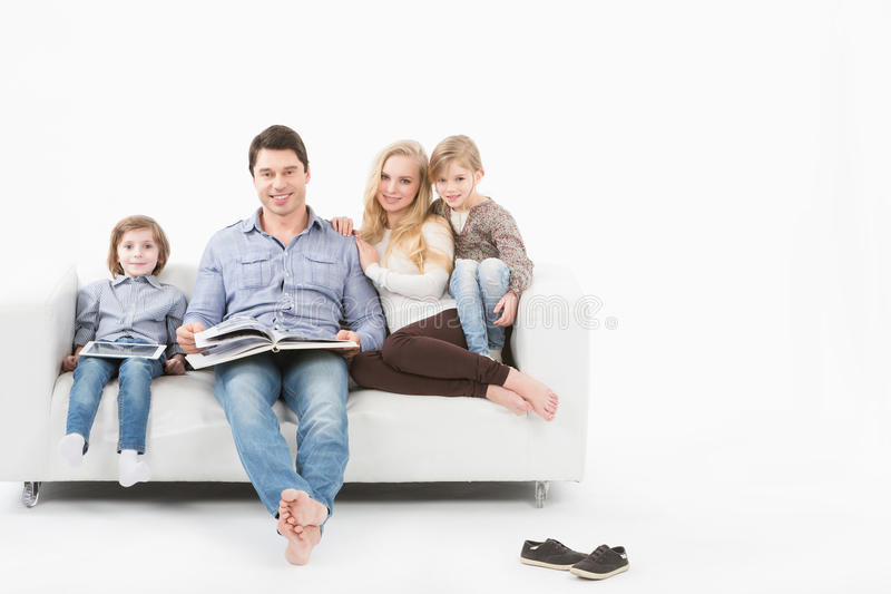 Amazing All Family Sitting On A White Sofa On A White Background And Reading A Book.