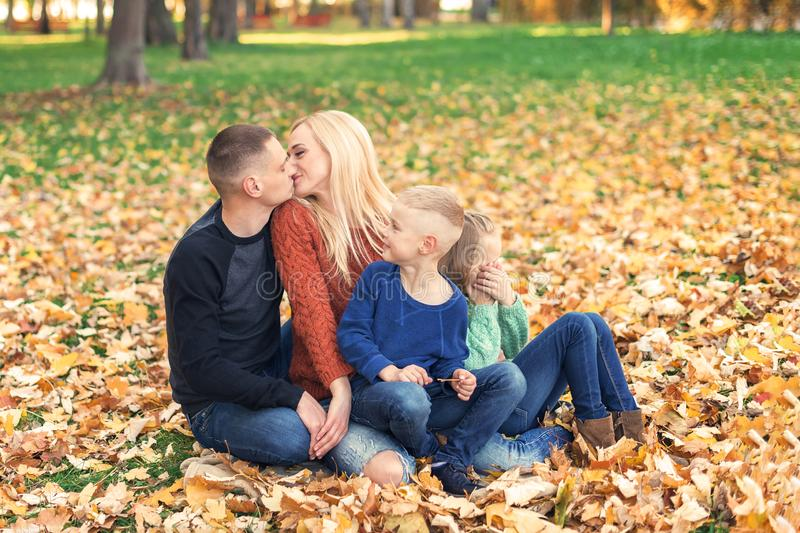 Happy family couple with children kissing in autumn park. royalty free stock photography