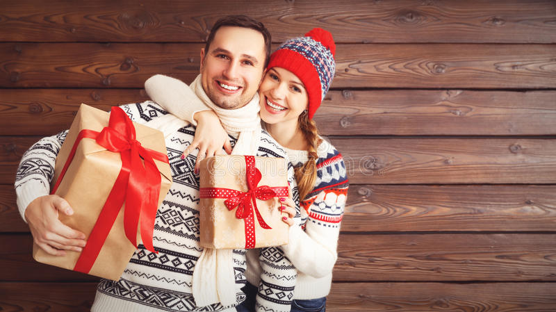 Happy family couple with Christmas gifts i on wooden background stock photo
