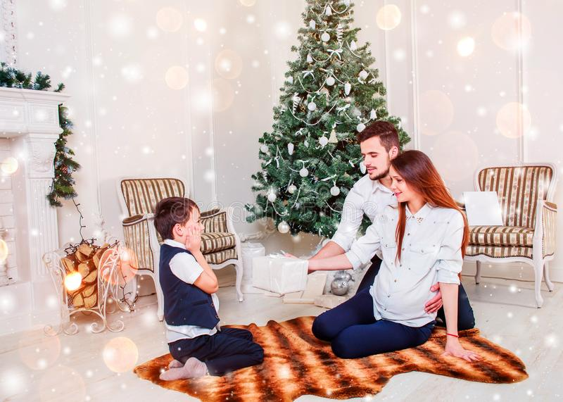 Happy family couple give gifts in the living room, behind the decorated Christmas tree, the light give a cozy atmosphere royalty free stock images