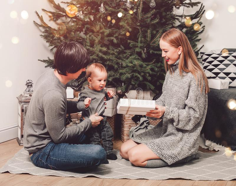 Happy family couple give gifts in the living room, behind the decorated xmas tree, the light give a cozy atmosphere. New Year stock photography