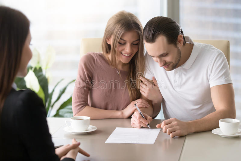 Happy family couple signing document, taking out bank loan, insu. Smiling couple agreed to sign prenuptial contract, handsome men putting signature on document stock image