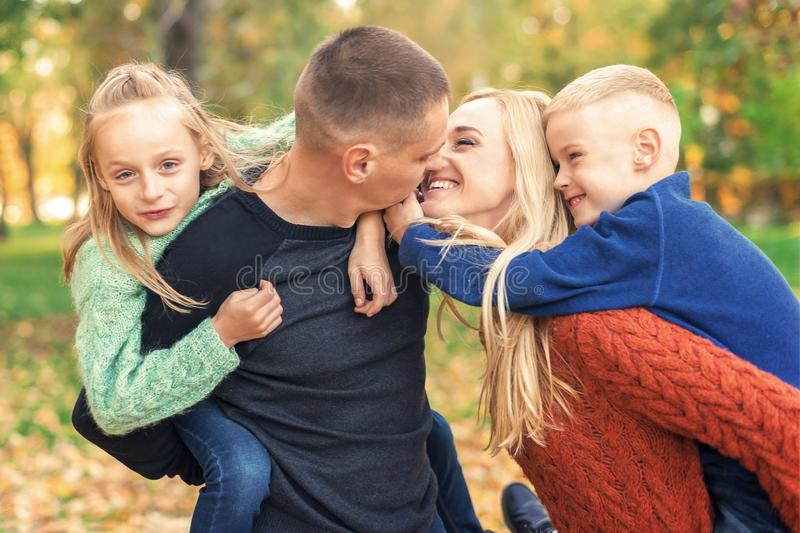Happy family couple with two children kissing in autumn park stock photo
