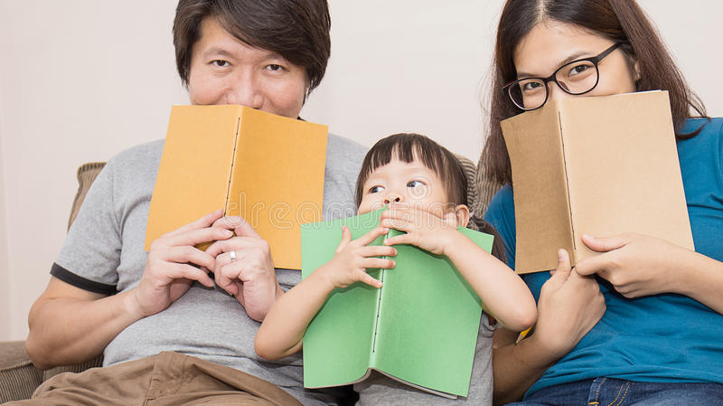 Happy family. Cute asian family with books cover on the faces, hide and seek stock photos