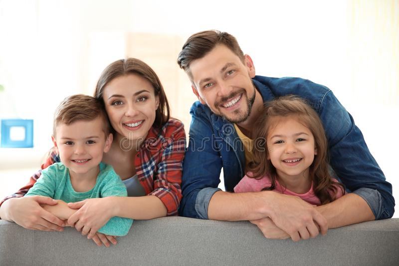 Happy family with cute children on sofa royalty free stock photo