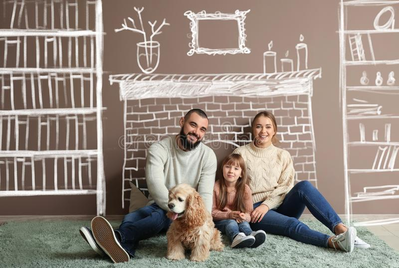 Happy family and cute dog on carpet near color wall stock images