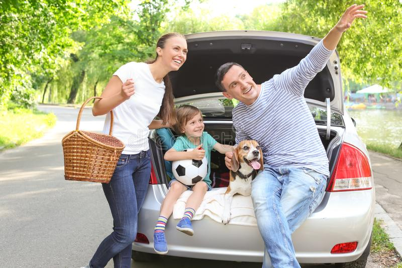 Happy family with cute dog near car outdoors stock photography