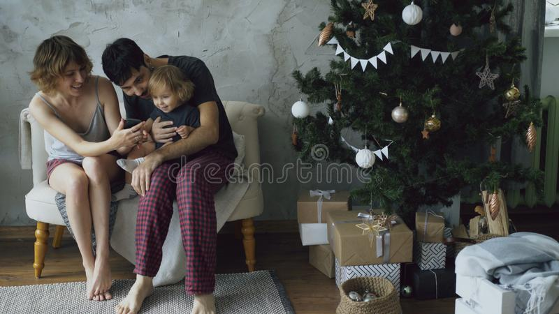 Happy family with cute little daughter sitting near Christmas tree and using smartphone at home stock photos