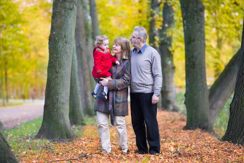 Happy family with cute toddler girl walking in park. Happy family with a cute toddler girl walking together in a beautiful park royalty free stock image