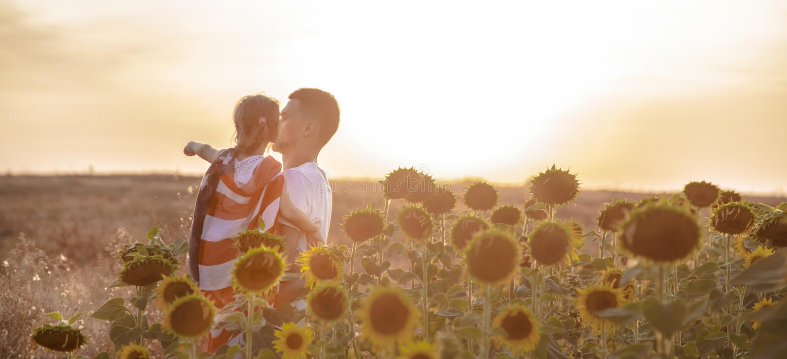A happy family with an American flag at sunset. Happy family, dad and daughter holding the American flag at sunset. Dressed in white. The concept of family royalty free stock photography