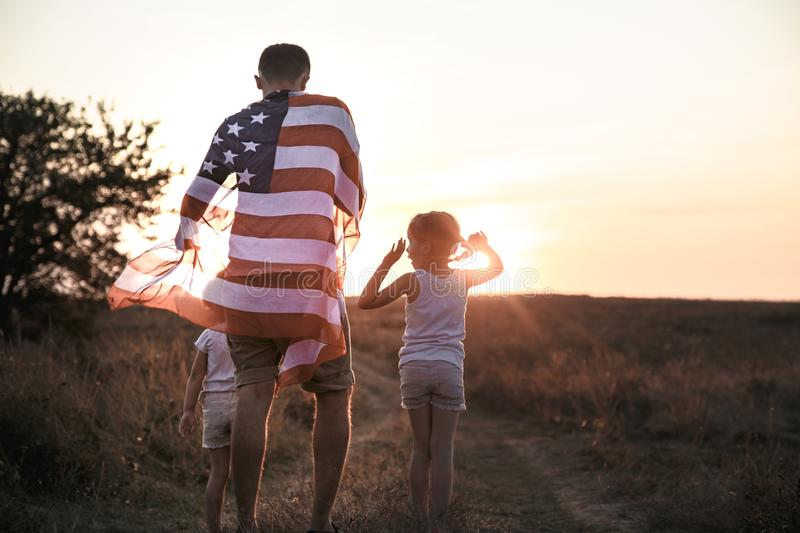 A happy family with an American flag at sunset. Happy family, dad and daughter holding the American flag at sunset. Dressed in white. The concept of family stock photos
