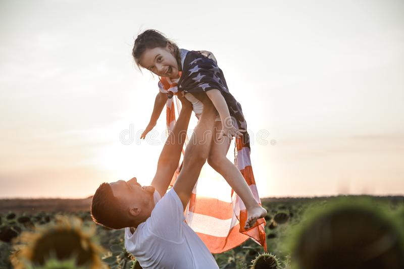 A happy family with an American flag at sunset. Happy family, dad and daughter holding the American flag at sunset. Dressed in white. The concept of family royalty free stock photos