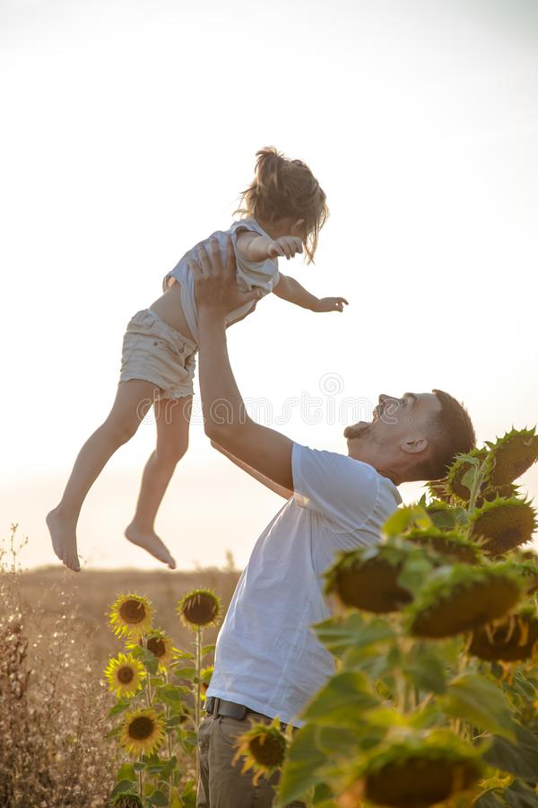 Happy family, father and daughter playing in the field. Happy family, dad with a little daughter playing in the field at sunset. The concept of family values and stock photo