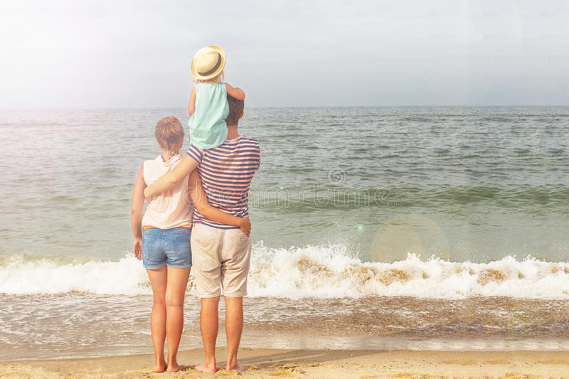 Happy family. Dad, mother and daughter are standing near sea. stock image