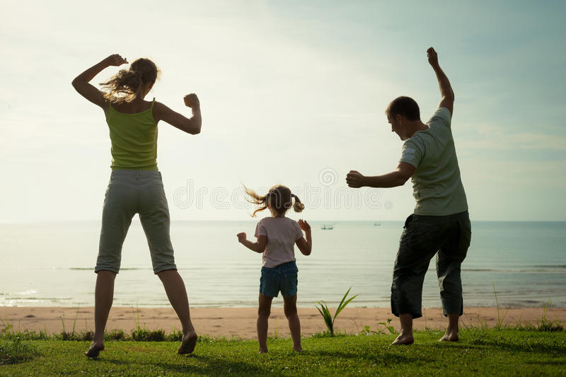 Happy family dancing the beach. On the dawn time stock image