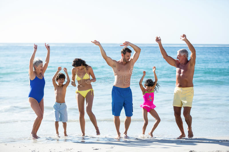 Happy family dancing on the beach. On a sunny day royalty free stock photography