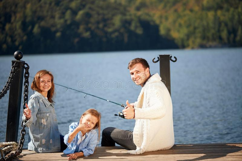 Happy family with daughter fishing in pond in fall stock images