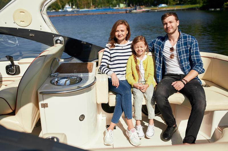 Happy family with daughter on sailing boat at sunny autumn day royalty free stock photo