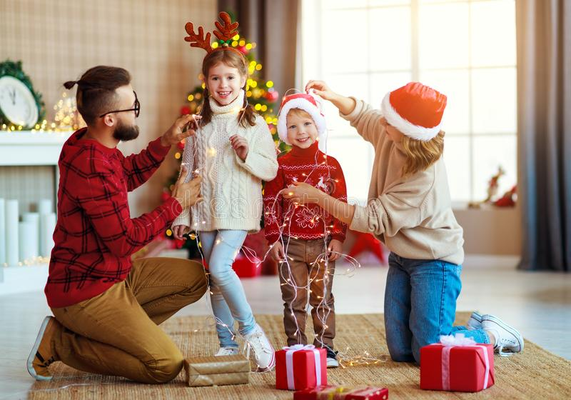 Happy family decorate Christmas tree, parents play with children with garlands royalty free stock photography