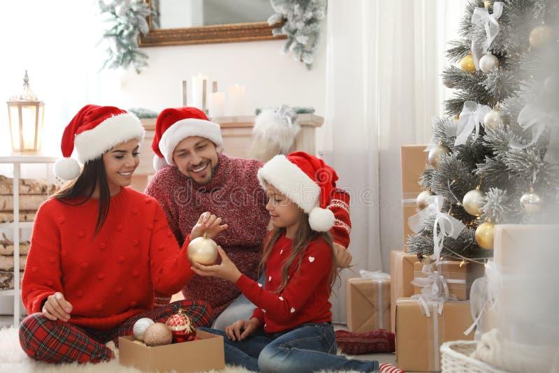 Happy family decorating Christmas tree stock photography