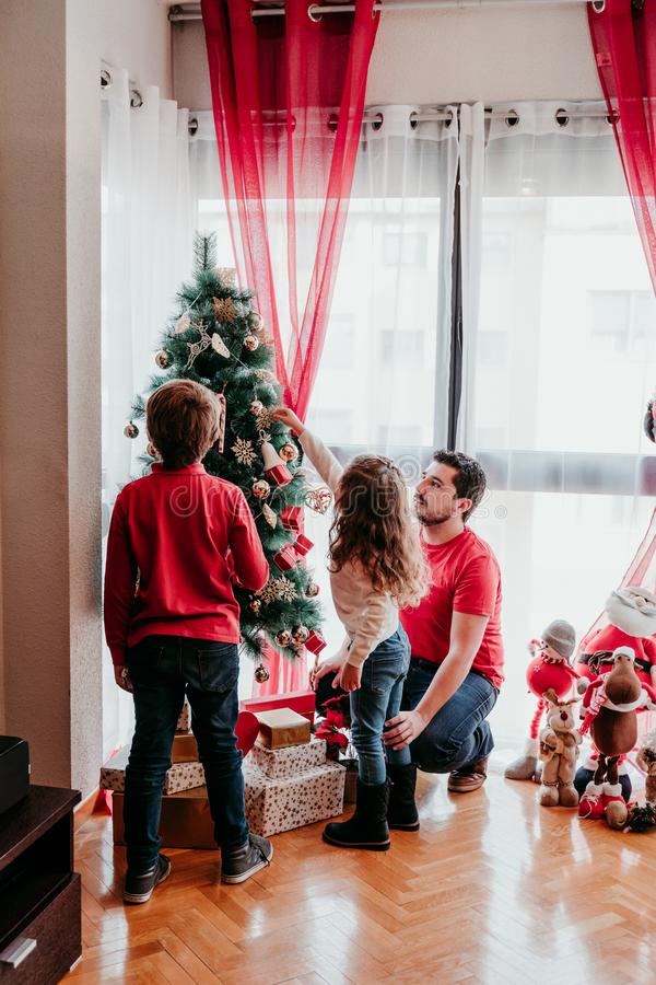 Happy family decorating christmas tree at home stock photography