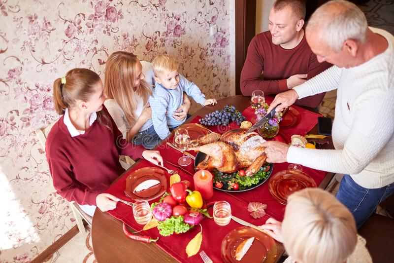 Happy family at the dinner table celebrating Thanksgiving on a blurred background. Traditional Thanksgiving concept. Multi-generation, cheerful family at the stock photo