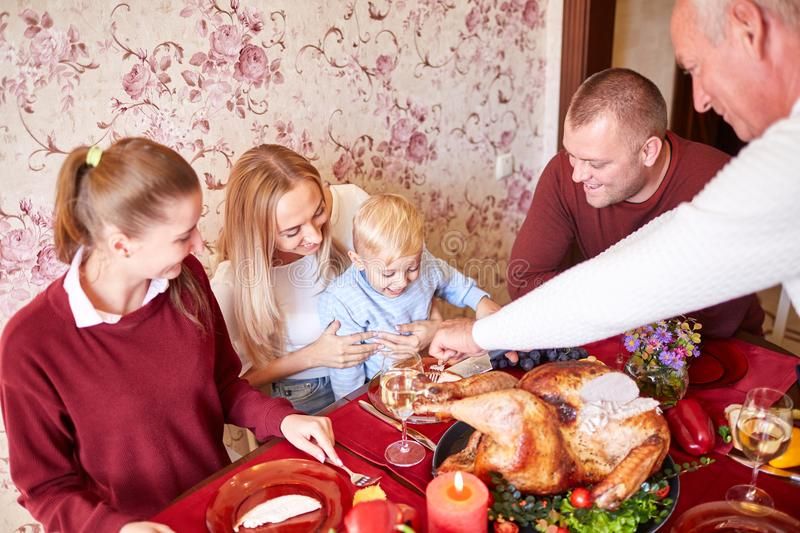 Happy family at the dinner table celebrating Thanksgiving on a blurred background. Traditional Thanksgiving concept. Multi-generation, cheerful family at the stock photography
