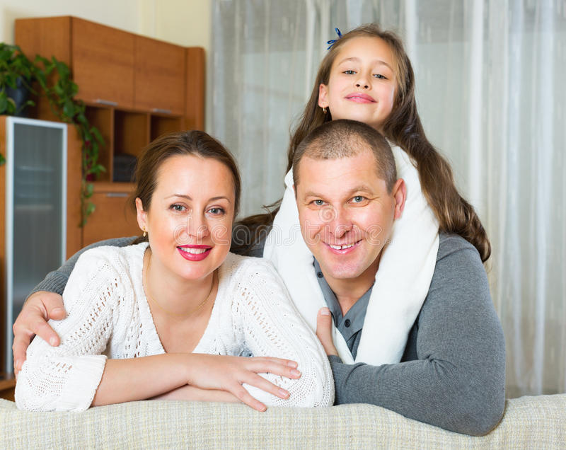 Happy family in domestic interior. Happy family of three in domestic interior at home royalty free stock photography