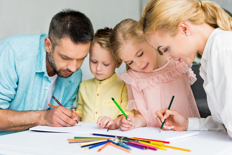 Happy family drawing with colored pencils together. At home royalty free stock photos