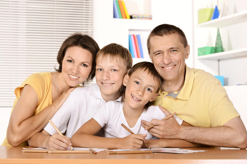 Happy family drawing. With colorful pencils at the table together royalty free stock photo