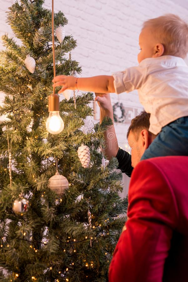 Young Happy Family Dressing Up The Christmas Tree. Back view stock photos