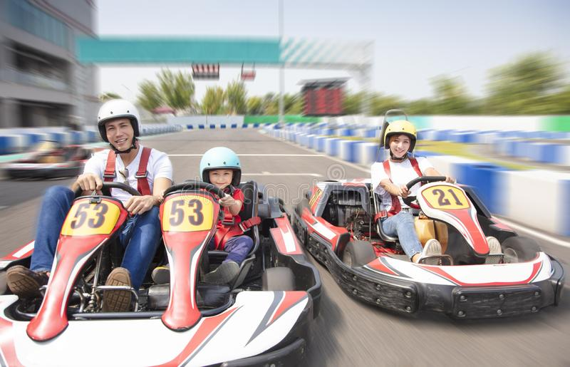 Happy family driving go kart on the track stock image