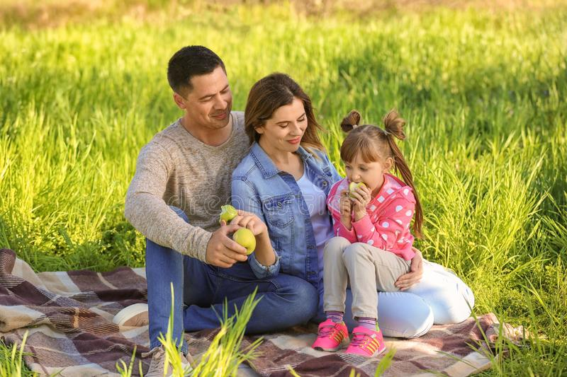 Happy family eating apples in park royalty free stock photography