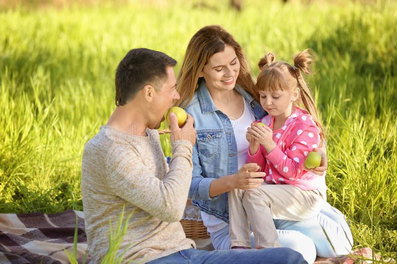 Happy family eating apples in park stock photo