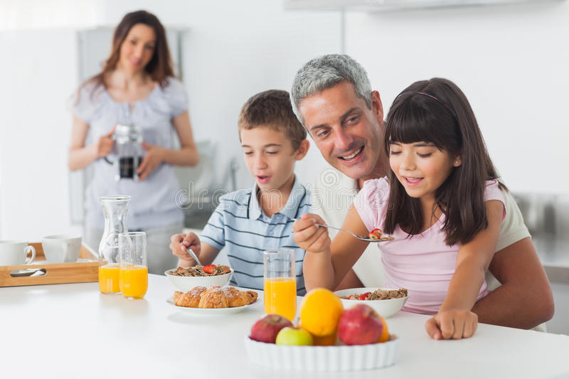 Happy family eating breakfast in kitchen together. At home stock photography